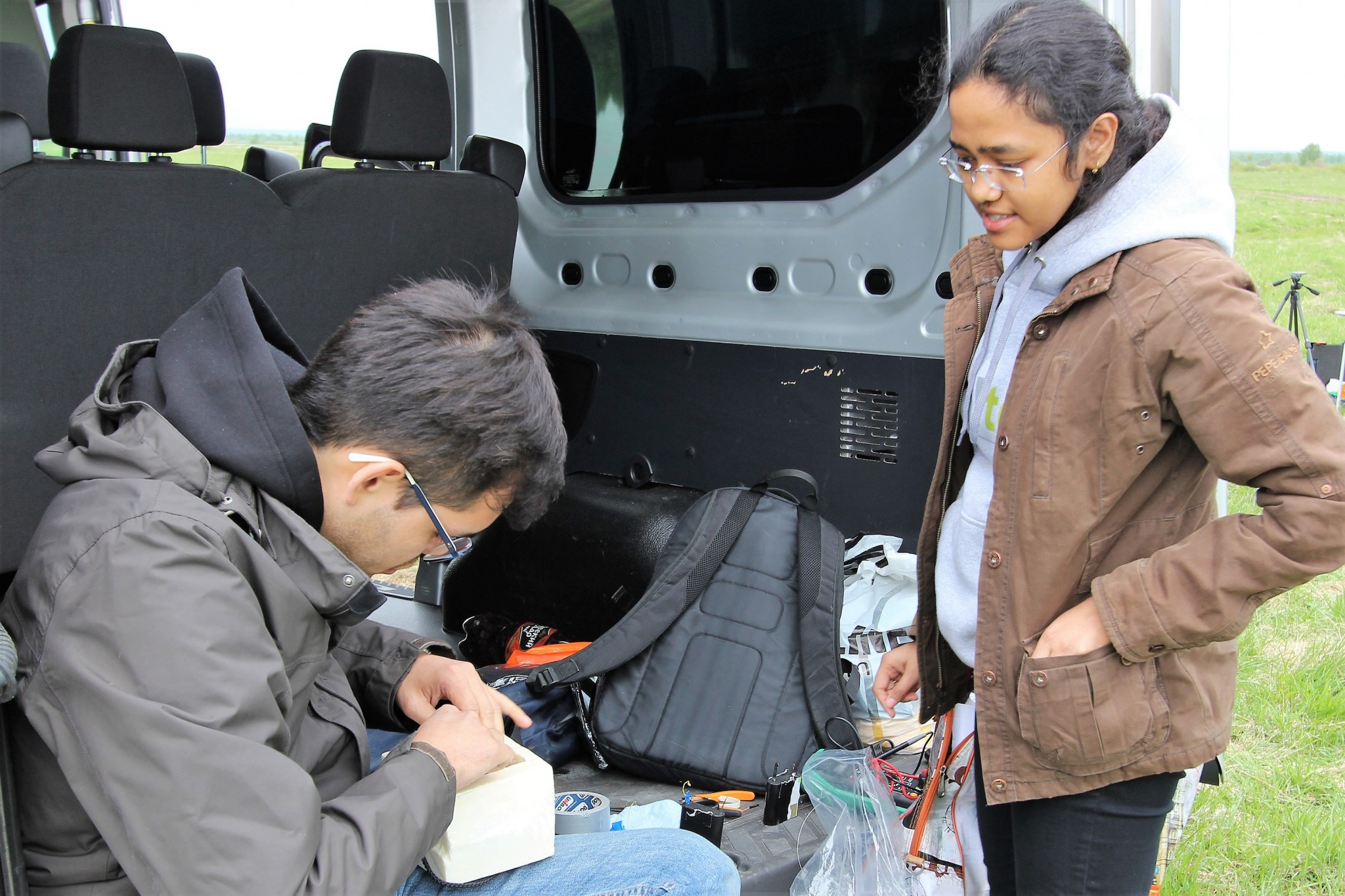 Miguel Cabrera and Shreya Santra use the back of a van as a workspace while preparing their team's payload. Photo: Skoltech.