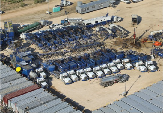 A typical footprint at a well site during a multistage fracturing job in North America, from a recent review paper on fracturing. Pump tracks are seen  in the center, connected to the main line going into the well, and trailers with the fracturing fluid on the perimeter. Photo: Custom Aerial Images
