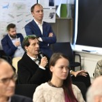 The audience pictured during a presentation, with organizer Rustam Kagirov pictured in the background. Photo: Skoltech.