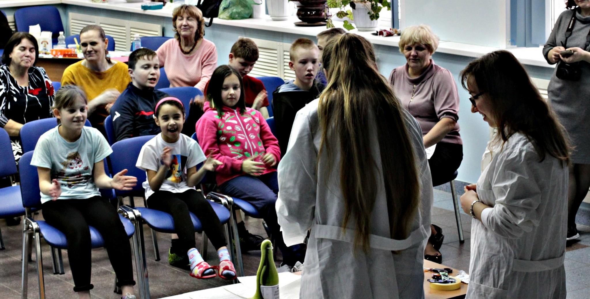 Skoltech students Julia Vasina (front left) and Valentina Ekimova amaze the children of the Mytishchi School of Musical Education with an experiment. Photo: Skoltech.