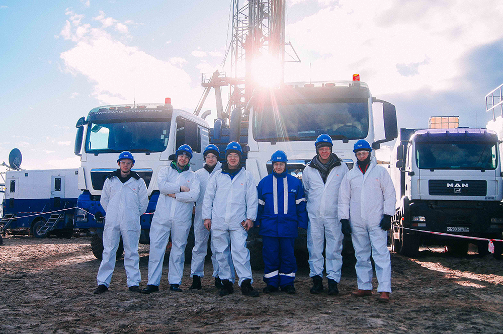 The team at the well site, with the drilling rig and hydraulic fracturing pumping tracks in the background.