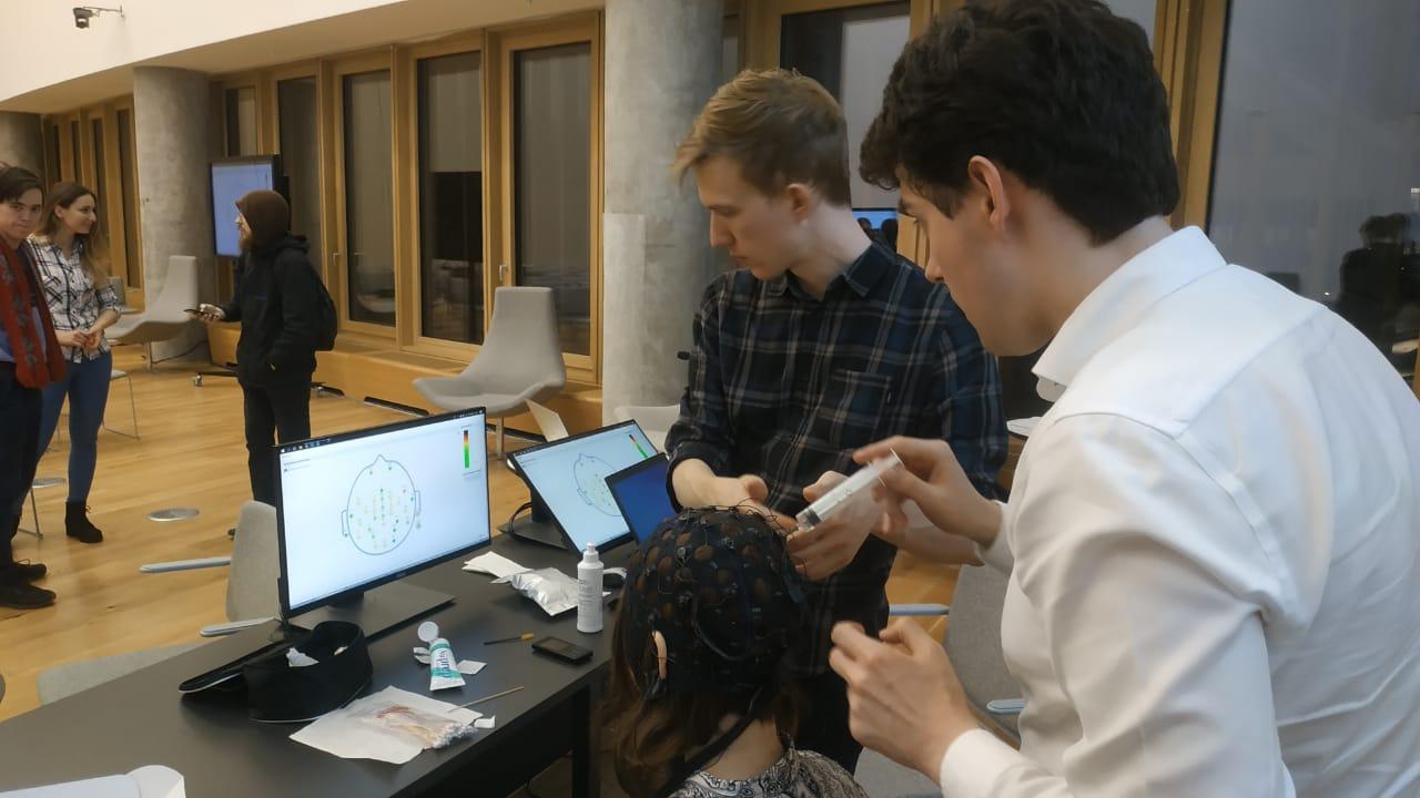 The seminar participants try on the BCI. Photo: Matvey Bulat (Skoltech)