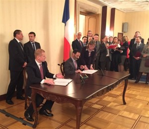 The agreement was signed by Nikolai Grachev, left, for Skolkovo, and Pierre de Firmas for EDF Group. Behind them, Alexei Ulyukaev, left, and his French counterpart Emmanuel Macron looked on.